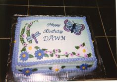 Butterfly in spring flowers birthday cake.  1/4 sheet frosted in buttercream with buttercream flowers.  Butterfly done in icing gels.