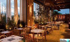 Projeto: Vitor Penha, Verônica Molina e Simone Balagué  Uma acolhedora varanda, com pé-direito alto e panos de vidro. Dos janelões se avista a copa das árvores. Mesas, uma cristaleira e um bufê vieram de antiquários. Transmite a sensação de tranquilidade. O ambiente rústico traz uma linda decoração retrô.  #DecoraçãoComercial #RústicoeModerno #DecoraçãoComercial #SãoPaulo #Restaurante #DecoraçãoIndustrial #Texturas #Iluminação #Revestimento #Varanda #PéDireitoDuplo #DanielKalilArquitetura