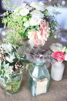 Bottles with feathers amongst the floral centrepieces