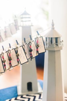 For a nautical themed wedding, hang escort cards on twine hung between two wooden lighthouses. Bonus: the rope key chains add a festive touch and are a great takeaway for guests.