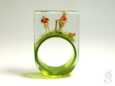 Wanderlust – jaunty climber figure ring with two mini hikers and a rabbit on a  green ring made of resin  ///// © Isabell Kiefhaber www.geschmeideunterteck.de