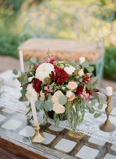 Burgundy & Ivory Flowers with Candles  Photography: Carrie King Photographer Read More: http://www.insideweddings.com/weddings/destination-rehearsal-dinner-and-welcome-party-in-sayulita-mexico/1045/