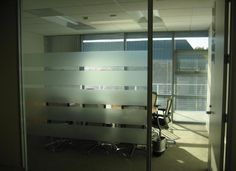 Frosted film adds privacy to offices Stripes of privacy frost give semi privacy to a glass walled office.