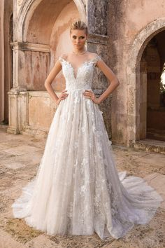 You will be a true bridal vision wearing this off the shoulder A-line gown. This dress showcases allover lace with 3D floral applique details. Button and loop closures adorn the back.