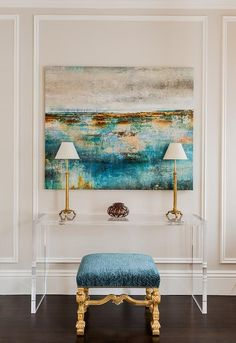 Chic foyer features a beige wall lined with decorative trim moldings lined with a turquoise and gold stool tucked under a lucite console table and a turquoise blue and gold canvas art piece.