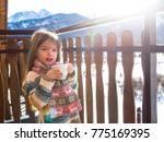 a little sweet girl is drinking tea on the background of the winter mountains in Zakopane,  Koscielisko, the concept of winter recreation