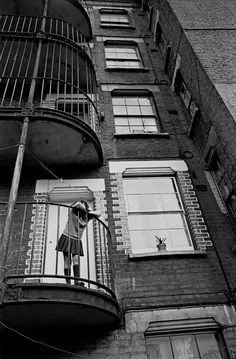 Child on balcony of her tenement block, Southwark | Nick Hedges 1970