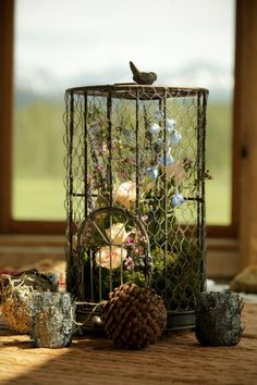 Gorgeous rustic birdcage with flowers and other natural details.  Could be worked into decor as a table centerpiece or other table decor.