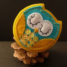 felt brooch by Lowe Sowe ...  adorable sleeping owl ,,, yellow, turquoise, white ,,, sequin breast feathers ... luv the pine cone perch ,,,