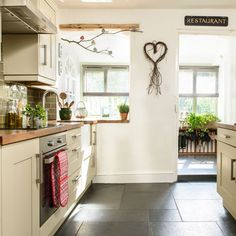 Cream country kitchen with twig artwork | 19th-century cottage in Devon | House…