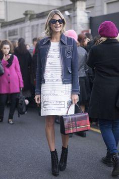 Helena Bordon no street style da Milan Fashion Week com jaqueta jeans pespontada, vestido com estampa gráfica, bolsa de mão com estampa xadrez, ankle boot preta e óculos escuros.