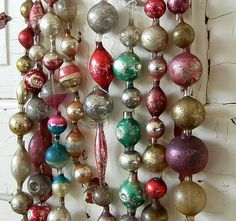 strings of vintage antique glass bulbs ! Love it!!! For Xmas trees or wrap in garland or drape like this the colours are so pretty!