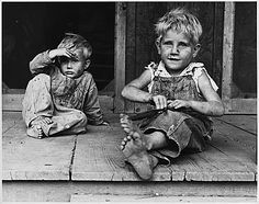 Picture of two very dirty looking children sitting on what appears to be a porch during the Great Depression. 1935