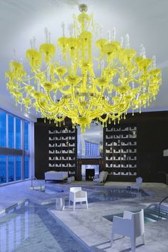 If this big, fluorescent yellow chandelier doesn't say bold, we don't know what does! Such a vibrant statement in this cool blue room. #yellow #blue #bold #chandelier