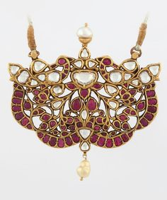 AN IMPORTANT DIAMOND AND RUBY PENDANT          Of openwork design, featuring two peacocks dancing in a flowering garden, kundan-set with rubies and rose-cut diamonds, suspending a single pearl, and with a single pearl surmount, with a total ruby weight of approximately 22.00 carats, a total diamond weight of approximately 8.75 carats, and a total pearl weight of approximately 1.34 carats, mounted in gold, suspended on an adjustable silk cord.