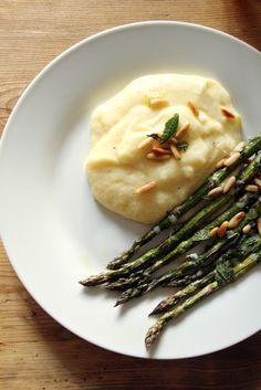 Cremige Polenta mit grünem Spargel aus dem Ofen, verfeinert mit Pinienkernen und frischer Minze