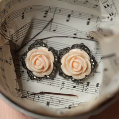 """peach blossom rose earrings $14.99  Cute rose petal earrings in a light peach with black rhinestone petals surrounding the rose. Wear in the evening or dress up a daytime outfit with these.  1"""" wide"""