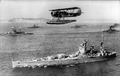 HMS Nelson seen in front of a squadron of other battleships or battle-cruisers of the Royal Navy, with a Blackburn Shark Seaplane flying overhead.