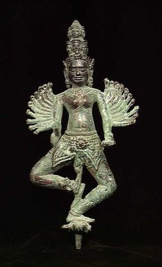 PUBLISHED KHMER BRONZE GODDESS, ca. 16th century. The goddess with 20 smaller arms issuing from her upper arms and wearing a loincloth dancing on two prostrate demons, and wearing a two tiered headdress bearing multiple heads, a mounting tenon on the base. 7 inches. Choice detail, style and condition with choice characteristic apple green Khmer patina.