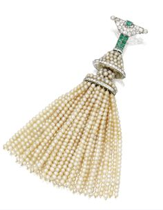 Platinum, natural pearl, diamond, and emerald tassel brooch, Cartier, France, circa 1915. The top set with small old mine and rose-cut diamonds, accented by small emerald-cut emeralds, supporting a tassel set with numerous natural pearl strands, natural pearls measuring approximately 2.8 mm., signed Cartier, numbered L5925, workshop mark, French assay marks.