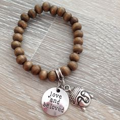 """Armband van 8mm bruine houten kralen met metalen plaatje met de tekst """"LOVE AND BELOVED"""" en een holle Boeddha. Van JuudsBoetiek; €8,00. Bestellen kan via juudsboetiek@gmail.com. Kijk ook eens op www.juudsboetiek.nl."""