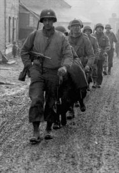 Soldiers of the 28th Infantry Division, U.S. Army, march down a street in Bastogne, Belgium, 20 December 1944 during the Battle of the Bulge. These men have been regrouped into security platoons for defense of the town.  The lead soldier is armed with an M3 .45 cal. sub-machine gun and an M1 Carbine over his shoulder.