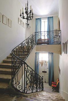 L'escalier central en pierre de Bourgogne, avec des lustres en fer forgé et en bois doré à la feuille dessinés par Henri Pouenat pour le Golf de Saint-Nom-la-Bretèche (78) ; gravures signées Pierre Brissart.