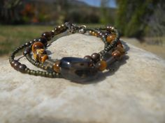 BR52. Triple-stranded bracelet with Japanese glass and brass beads with smoky quartz centrepiece. Smoky quartz clasp detail. $25. https://www.facebook.com/photo.php?fbid=218881318273871&set=a.141503356011668.29288.141493752679295&type=3&theater