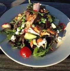 KIPSALADE MET FETAKAAS Versier je groene salade met gegrilde kip, koeienkaas/fetakaas, amandelen, rauwe aubergine, tuinkers, bosui, radijs en cherrytomaat. Maak de salade af met een lichtzoete gemberdressing. Enjoy!