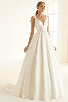 Jessica is an a-line wedding dress made of high-quality satin. Similar to Julia, Jessica has a deep v-neckline and back with strong, bold pleats at the front. Closed with discrete back-zip fastening and a long train, Julia is a chic and classic wedding dr Classic Wedding Dress, New Wedding Dresses, Cheap Wedding Dress, Designer Wedding Dresses, Bridal Dresses, Wedding Dress Bolero, One Shoulder Wedding Dress, Bridal Dress Design, Bridal Boutique