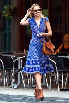 Candice Swanepoel looks boho chic in a midi dress, brown ankle boots and crossbody bag for her off-duty look.