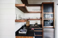 L shaped kitchen pantry is filled with wood cabinets fitted with black drawer fronts paired with black quartz countertops and a white shiplap backsplash.