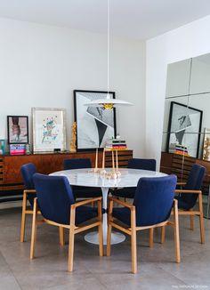 Sala de jantar tem aparador vintage, cadeiras azuis e mesa Saarinen.