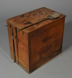 Shaker Wood Box, Hancock, Massachusetts, c. 1820, the hinged lid opens to a divided interior, the dovetail construction box with wrought iron harp-shapped hangers mounted to the left side, and wooden knobs on each side, sold with a pair of wrought iron tongs and a small peel, 25 H. x 26 W. x 17.5 D.