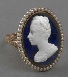 Ring with tassie depicting Queen Charlotte (1744-1818). Gold ring with chased shoulders, bezel set with a tassie cameo left profile portrait of Queen Charlotte on blue enamel ground, within a border of seed pearls.