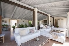 Rustic - A seating area with white-upholstered furniture, throw pillows, a beige throw, and low coffee tables