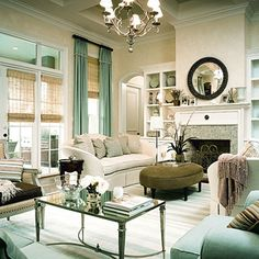 living room - French Mirrored Coffee Table gray green oval velvet ottoman white sofas black mirror blue green glass tiles fireplace chandelier seafoam green silk drapes bamboo roman shades window treatments blue white striped rug built-ins seafoam green velvet chairs
