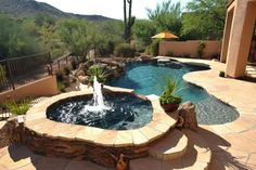 Beautiful natural #pool with raised #spa, #fountain feature, rock #waterfalls, lounging shelf, built in umbrella stand and #flagstone decking. http://calpool.com