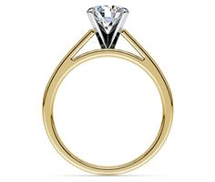 This charming yellow gold solitaire engagement ring setting features a flat band design that extends gracefully on either side to frame your stone. White gold prongs secure your choice of center diamond.