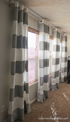 striped gray curtains. Painted! Buy plain white curtains and Paint them. Use painters tape to tape off the size of stripes you want, lay the curtain on plastic, and paint with a roller!