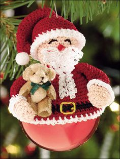 Adorable Crochet Santa topper sitting on a round glass ornament. FREE PATTERN