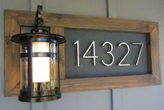 house numbers Barn wood frame & contrasting background and by light so it's easy to see at night - make it out of the iron so that it lasts long and put Street below it in small letters. Have the background be sheet metal painted black. Paint removable/interchangeable cream painted iron numbers onto the sheet-metal.