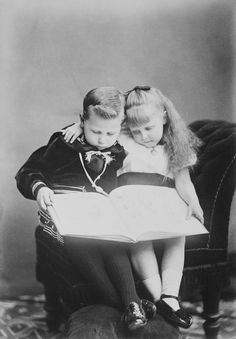 Prince Alfred (left) and Princess Marie (right) sit together. Both look down at large book open on their laps. Prince Alfred in sailor suit, Princess Marie in short-sleeved dress with wide sash.