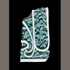A Timurid carved turquoise pottery tile fragment, Samarkand, second half of the 14th Century