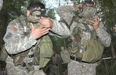 From left, U.S. Army Pfc. Francis Provenzano and Spc. Jess Hampton, both from Alpha Company, 3rd Battalion, 21st Infantry Regiment, 1st Stryker Brigade Combat Team, practice putting on their M24A2 gas mask while preparing to enter the chemical, biological, radiological and nuclear testing station during the expert infantryman badge competition at Fort Wainwright, Alaska, July 26, 2007. (U.S. Army photo by Spc. Tiffany L. Evans)