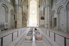 Nave of the Romanesque abbey church (1105-60), looking east. The polychrome tombs in the foreground are those of King Henry II Plantagenet (d. 1189); Eleanor of Aquitaine (d. 1204), Henry's queen; King Richard I the Lionheart (d. 1199), their son; and Isabella of Angouleme (d. 1246), the wife of their youngest son, King John (d. 1216). Abbey of Fontevraud, Loire Valley, France.