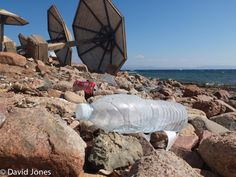 A plastic bottle sits alongside umbrellas on the coastline