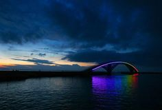 The Xiying Rainbow Bridge an elevated pedestrian walkway located in Magong, Penghu County in Taiwan. The bridge is lined with a thin neon band that reflects a rainbow onto the water's surface below at night Destinations, Rainbow Light, Bridge Design, To Color, Rainbow Bridge, Color Photography, Oh The Places You'll Go, Installation Art, Architecture