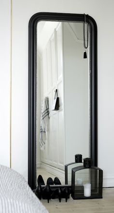 black framed mirror really makes a statement in a all white room
