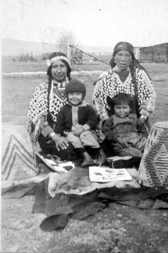 Yakama two women sit with a child on each of their laps. Around them are placed pelts, baskets and beadwork. They wear a headband or scarf and decorated blouses.